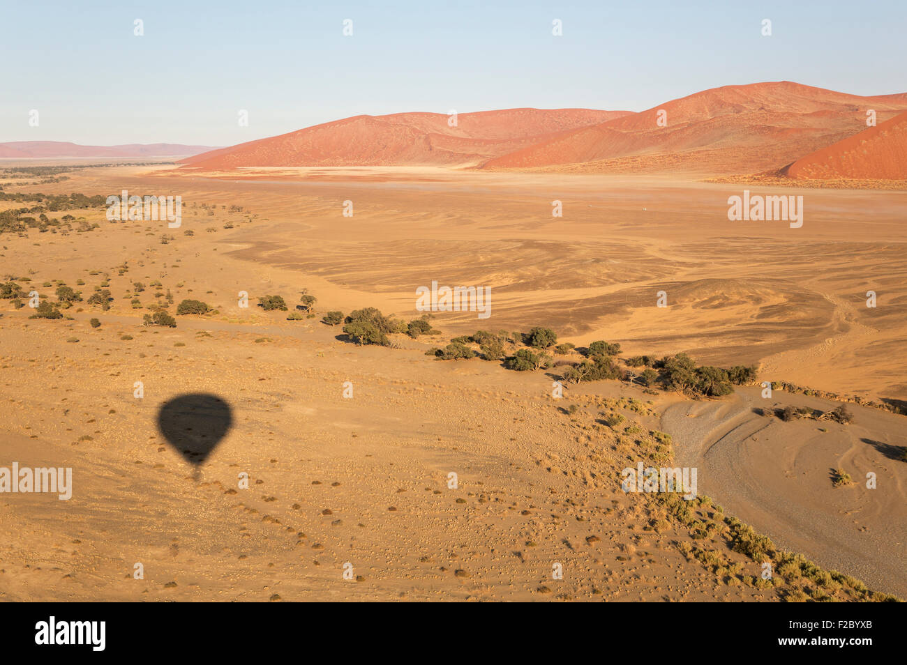Shadow of the hot-air balloon over an arid plain and the dry riverbed of the Tsauchab river at the edge of the Namib - Stock Image