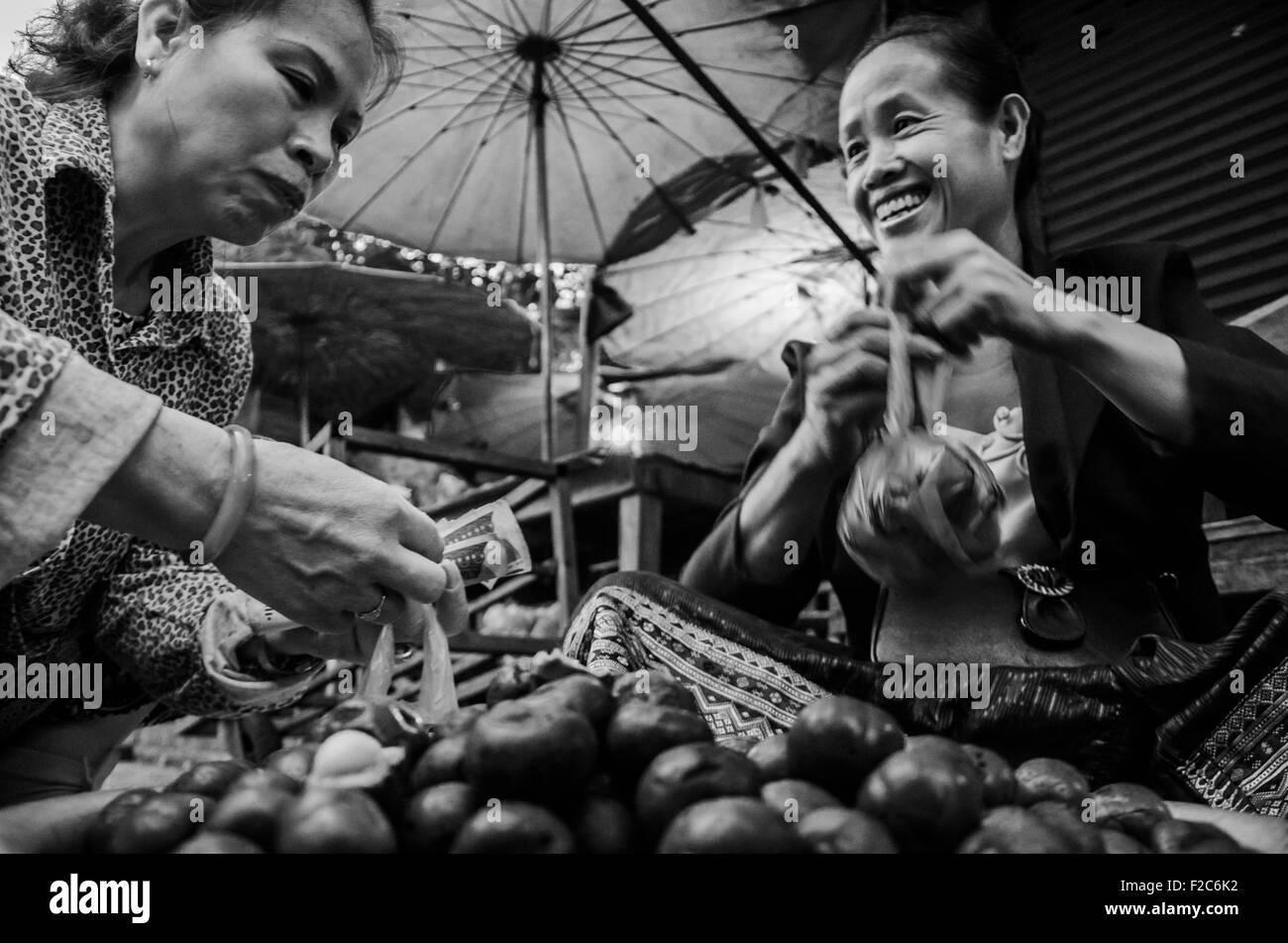 Luang Prabang, Laos. 3rd Apr, 2014. Luang Prabang, Laos - April 3 2014: (EDITORIAL USE ONLY. CHINA OUT) Giving and - Stock Image