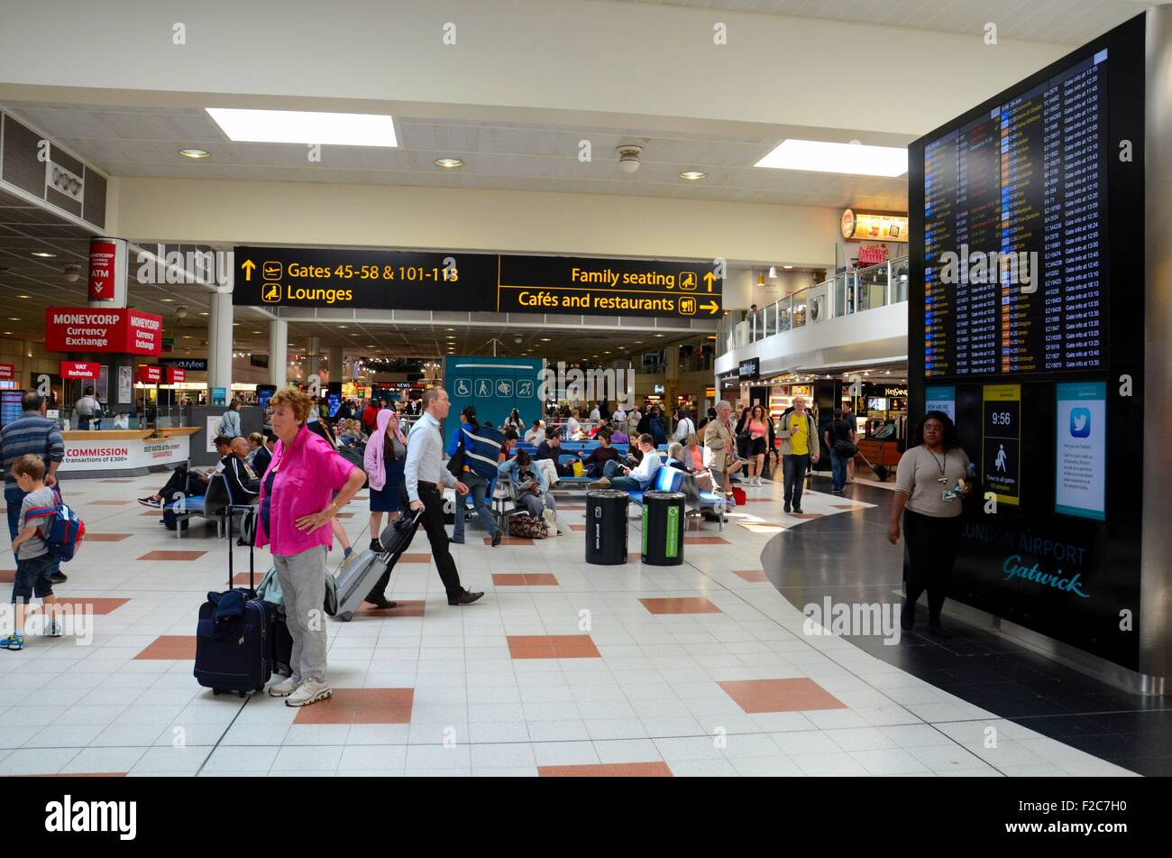 Travelers and people at England's London Gatwick Airport departure lounge with flight display - Stock Image