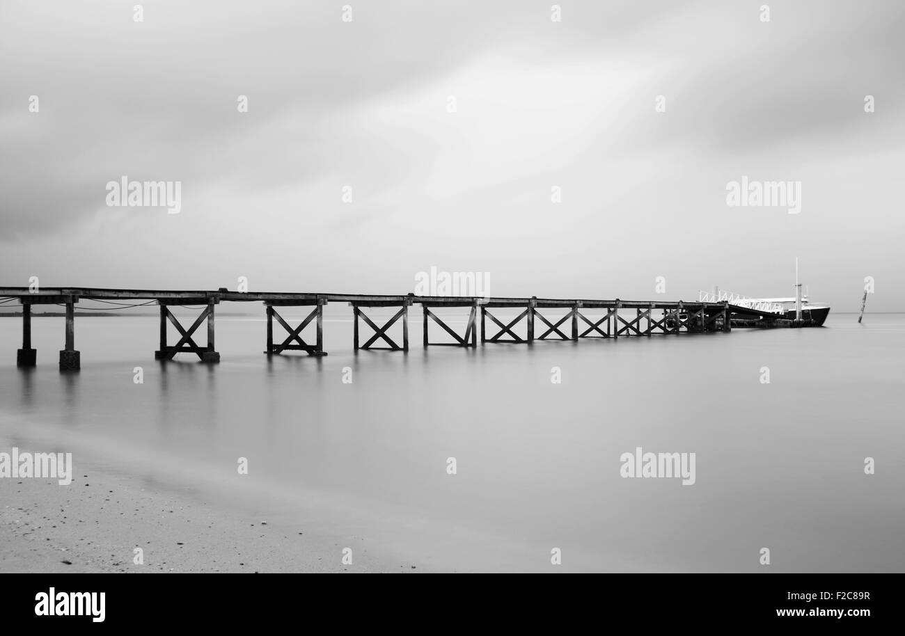 Black and white of pier on a cloudy day - Stock Image