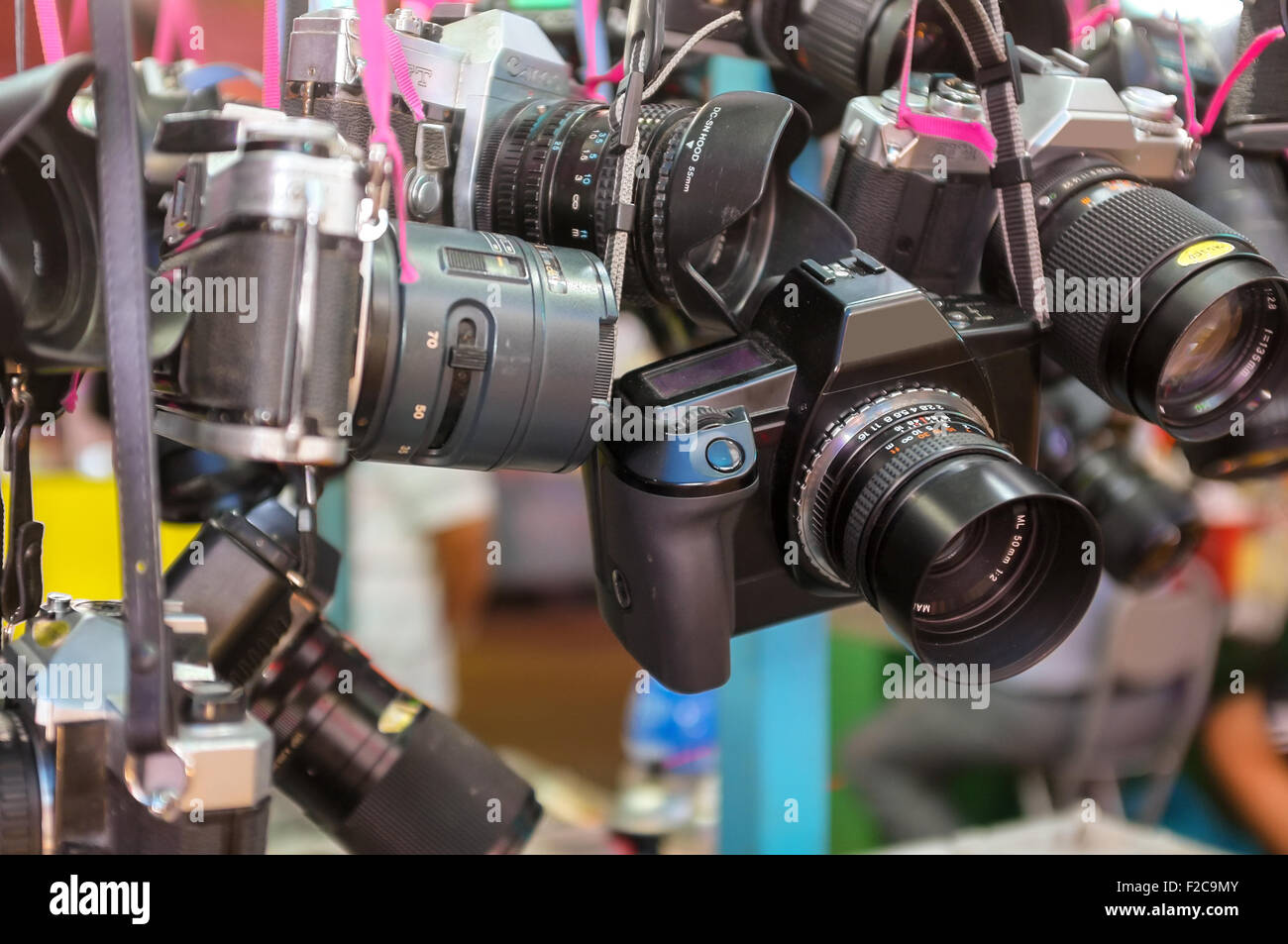 Old cameras hanging up for sale at an outdoor market in Hong Kong - Stock Image