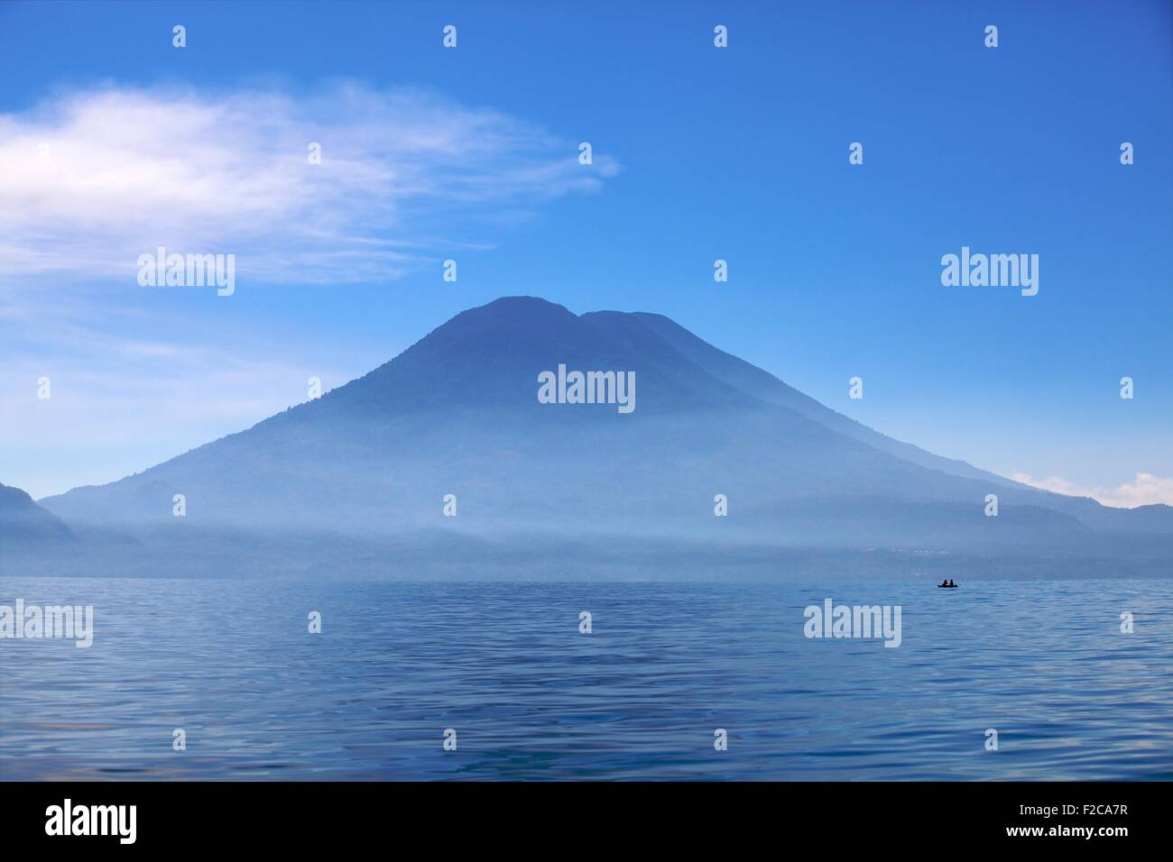 Deep blue: Lake Atitlan a small boat in silhouette against Tuliman volcano Stock Photo