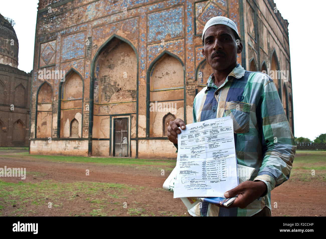The descendant of a Bahmani king is showing his genealogy tree in front of the tomb of one of his ancestors ( India) - Stock Image