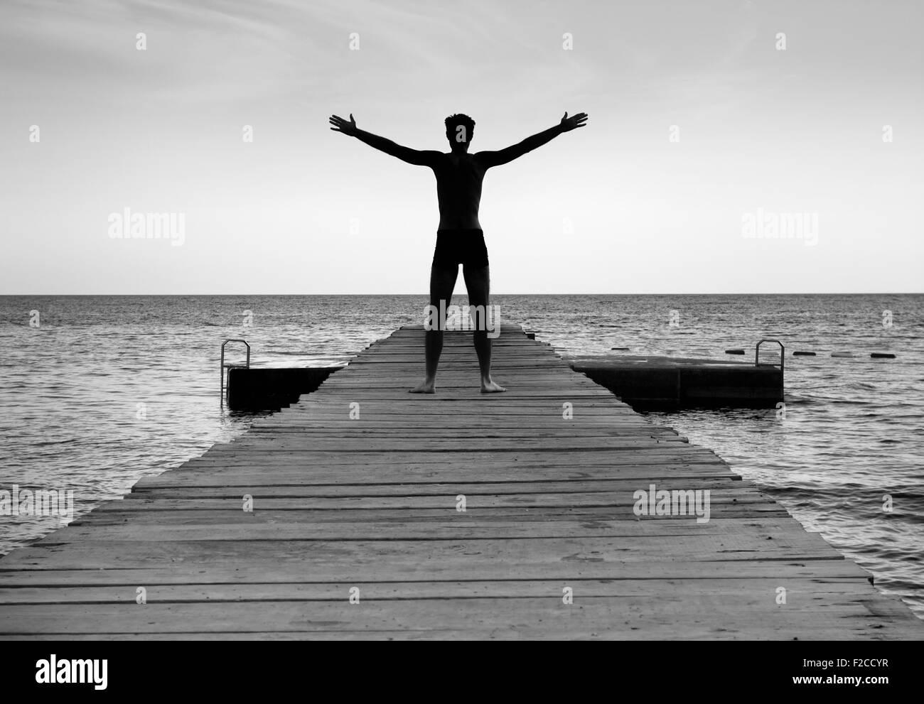 Silhouette of free peaceful man on sea pier - Stock Image