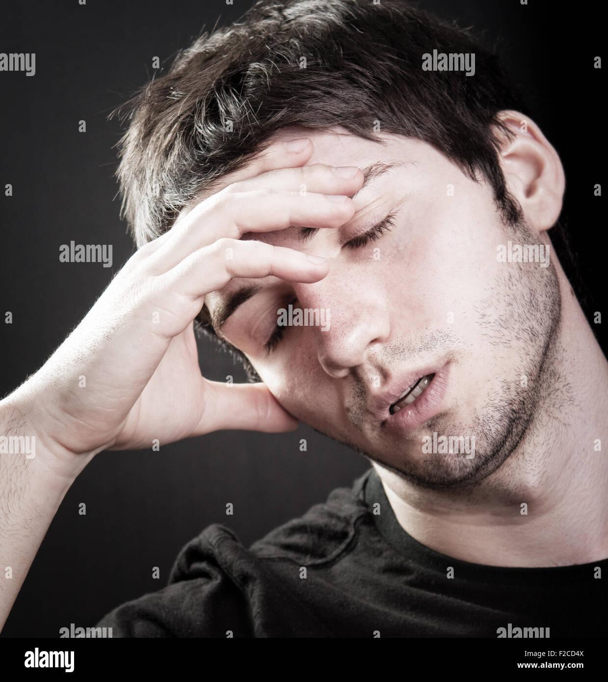 Depression concept - sad young man over black - Stock Image