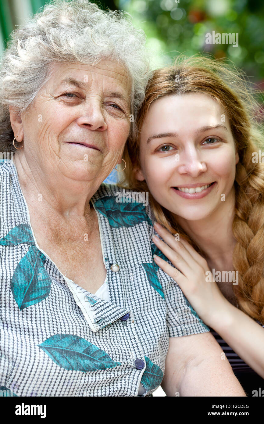 Family portrait of joyful young woman and her grandmother - Stock Image