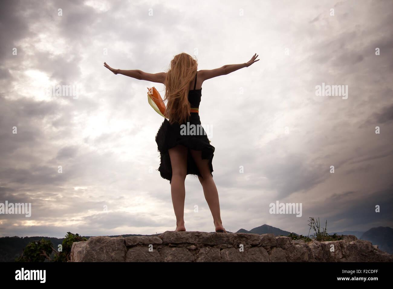 Freedom concept - adventurous woman on mountain peak - Stock Image