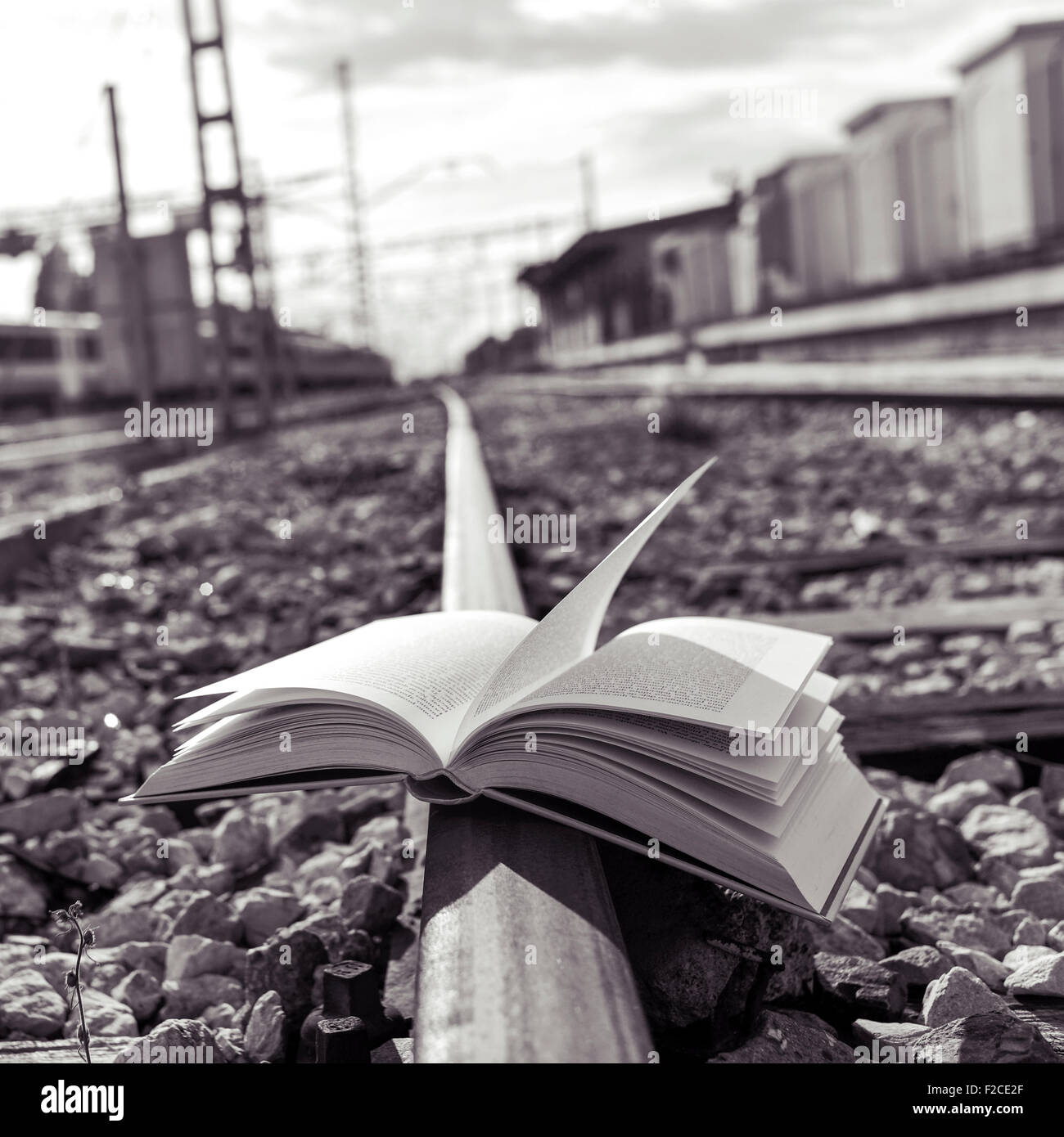 closeup of an open book on the railroad tracks, in black and white - Stock Image