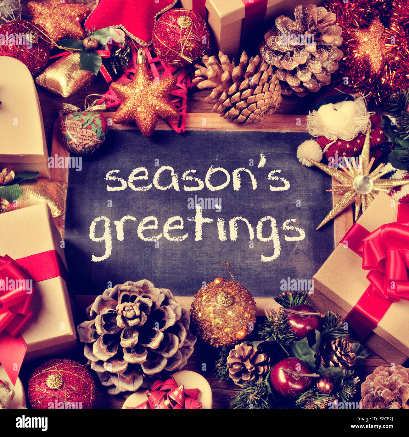 The text seasons greetings written in a chalkboard surrounded by the text seasons greetings written in a chalkboard surrounded by some gifts and a pile of different christmas ornaments such as m4hsunfo