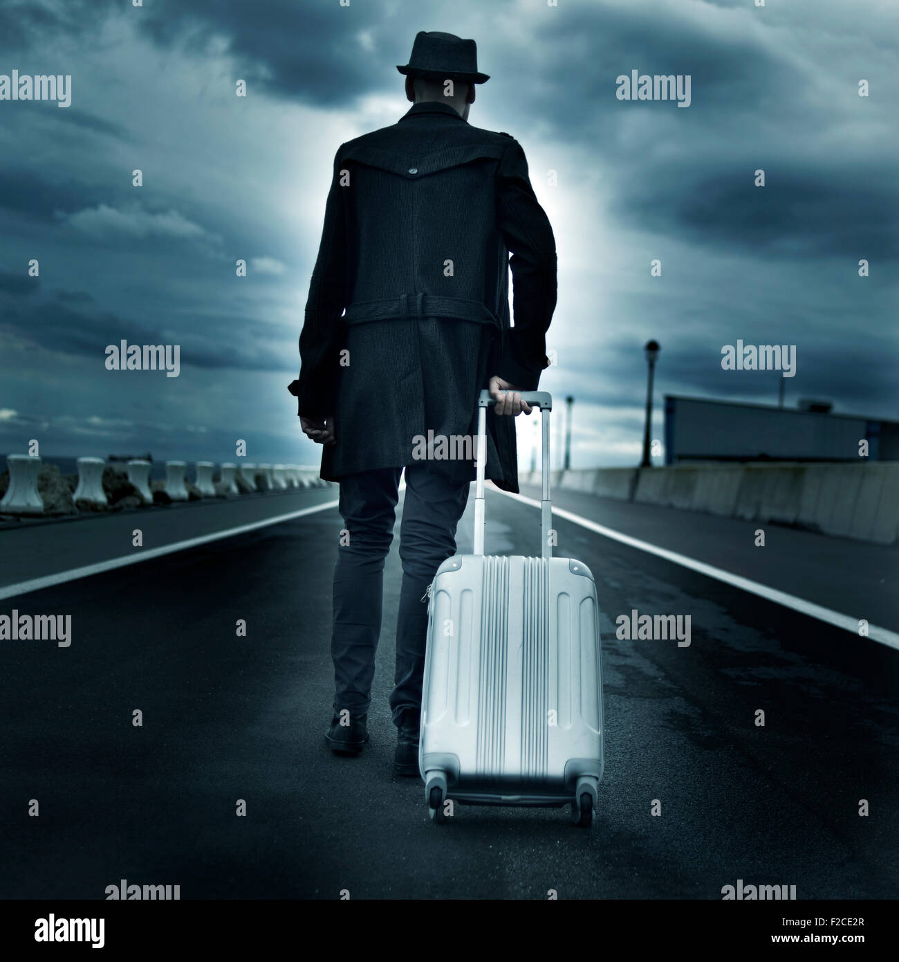 closeup of a young man seen from behind carrying his rolling suitcase, with a dramatic effect - Stock Image