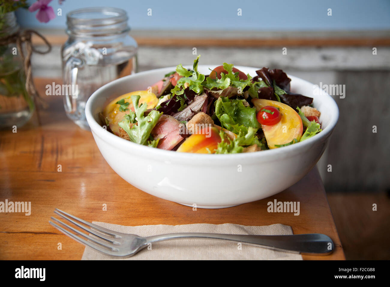 Side view of salad in white bowl with fork, napkin, - Stock Image