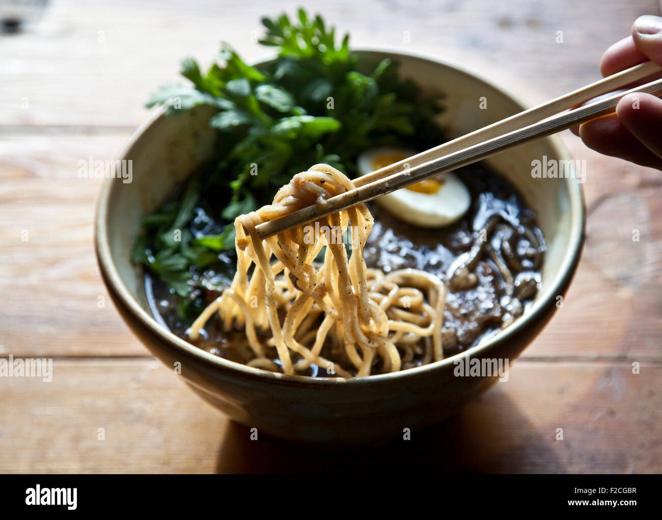 overhead view of ramen with hand holding chop sticks and noodles Stock Photo