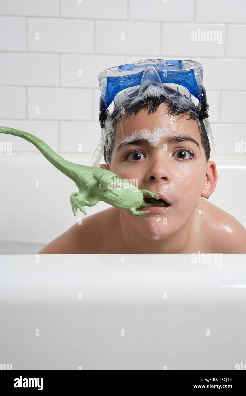 young boy in bathtub with goggles on top of his head and plastic dinosaur in mouth with soap suds looks at camera - Stock Image