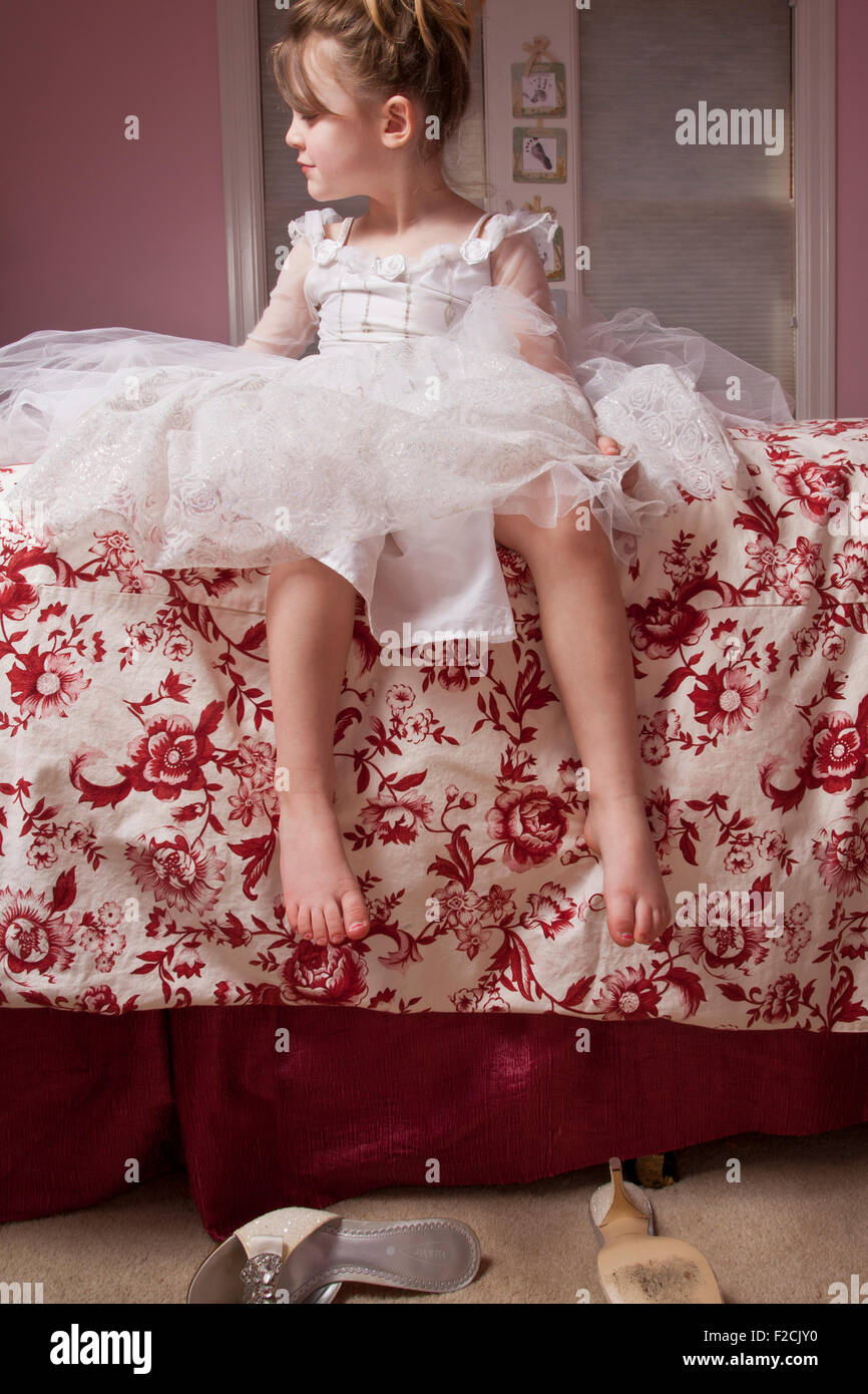 Young girl sits on bed looking to her right in frilly dress - Stock Image