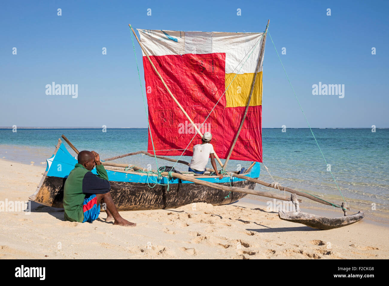 Two fishermen with traditional fishing pirogue with sail on beach at Nosy Ve, Madagascar, Southeast Africa - Stock Image