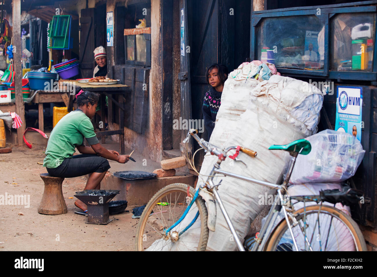 Malagasy woman cooking on charcoal in the dusty shopping street of the city Ambalavao, Haute Matsiatra, Madagascar, - Stock Image