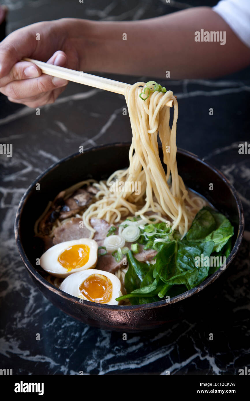unidentified woman holds chopsticks with ramen, egg, spinach, porkbelly - Stock Image
