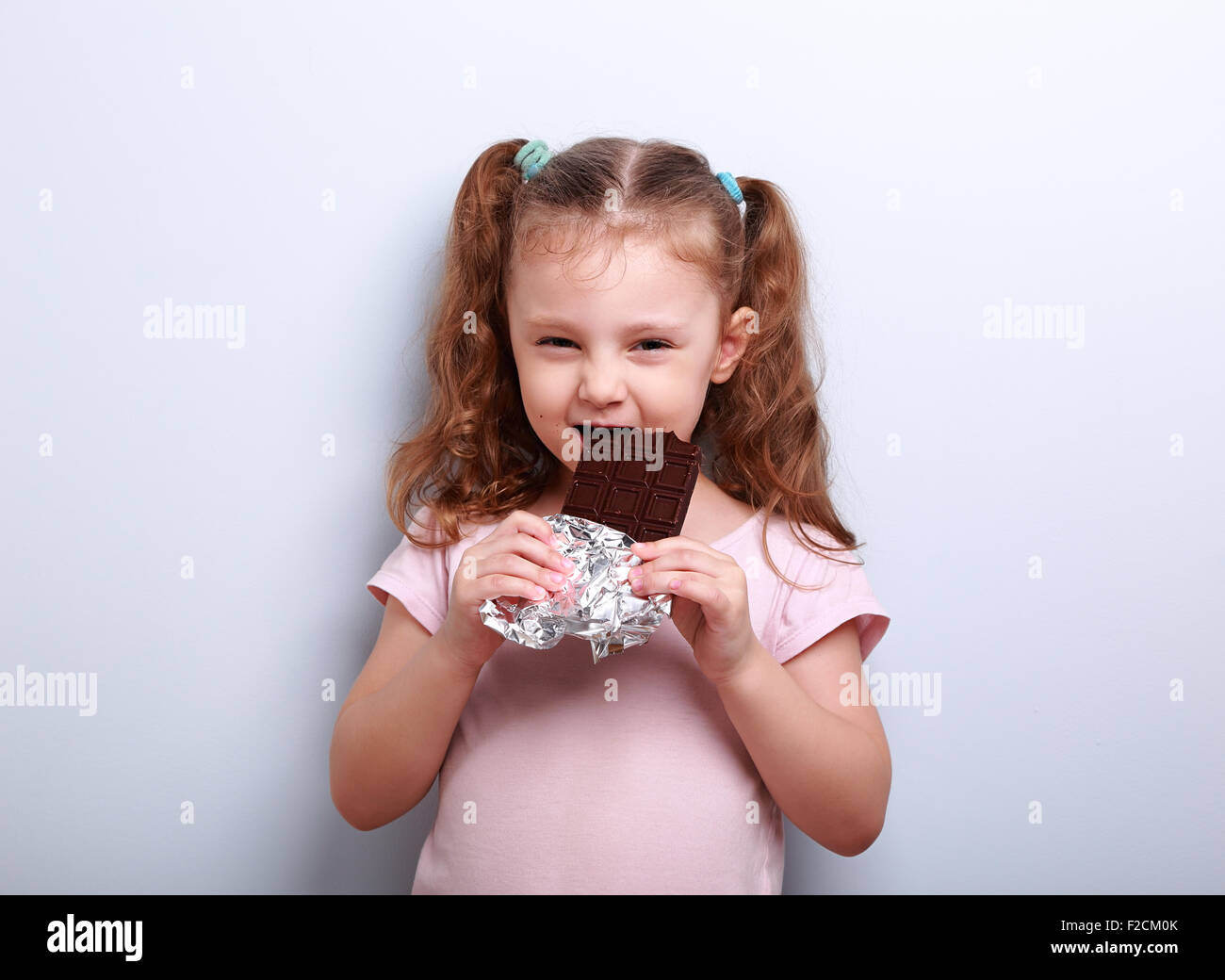Cunning fun kid girl eating dark chocolate with curious look on blue background - Stock Image