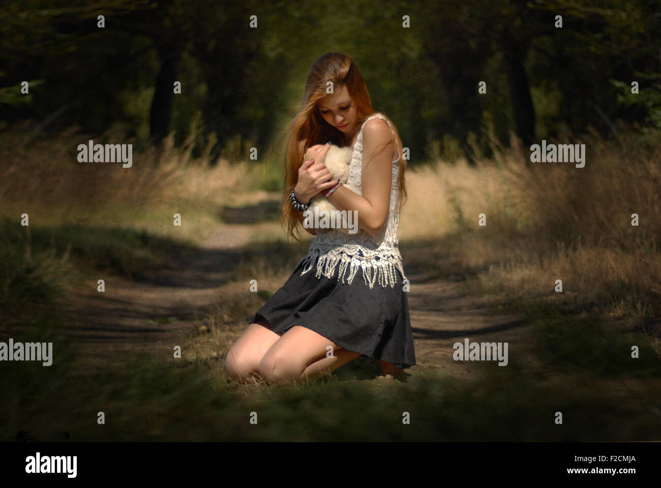 Lost soul and innocence - girl hugging teddy bear in forest crying girl in the forest with teddy bear  beautiful - Stock Image