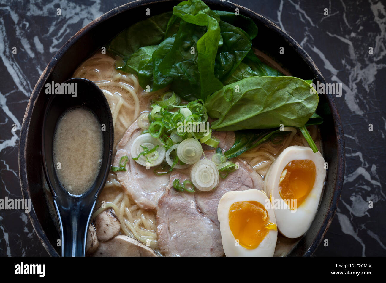 Overhead view of bowl of ramen with with egg, spinach, pork and pork belly - Stock Image