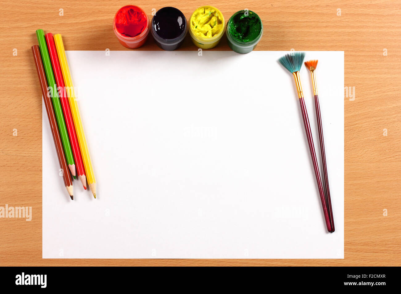 Empty sheet, paint and pencils on desk, creativity concept - Stock Image