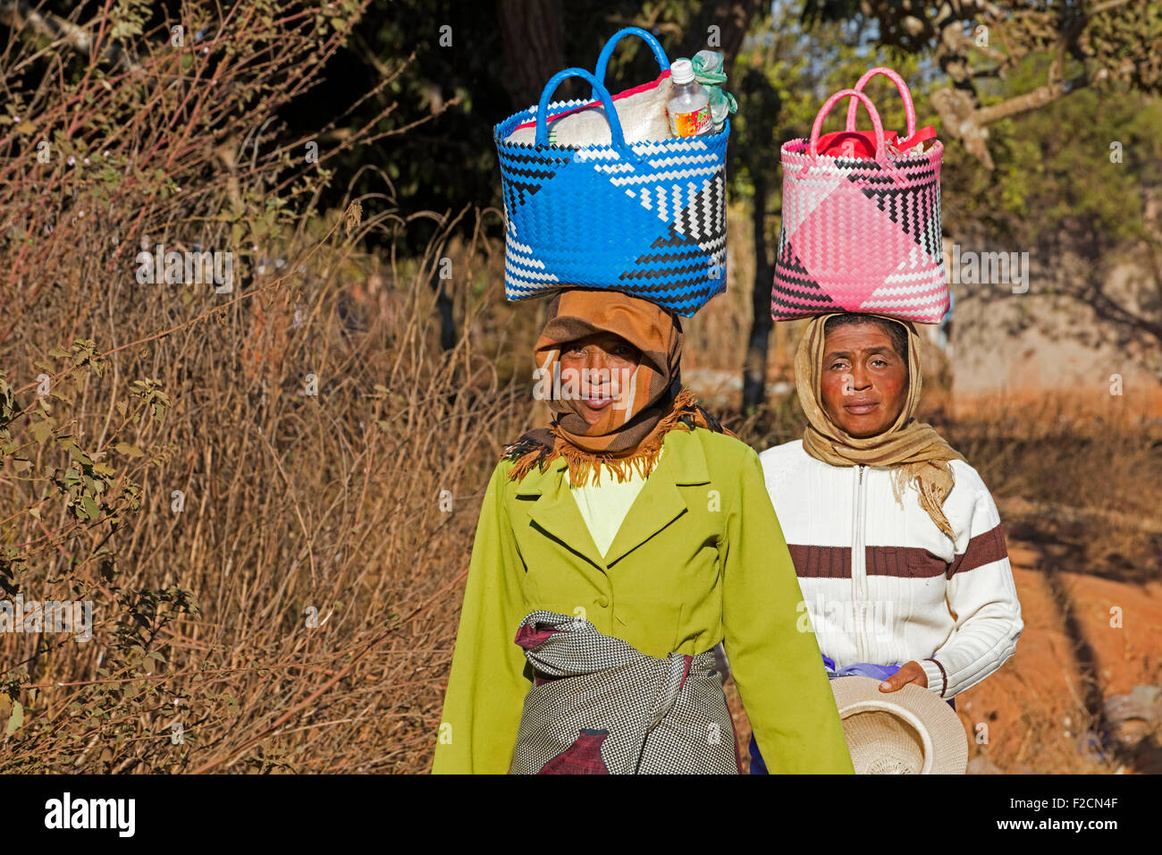 Two Malagasy women with shopping bag on their head walking to weekly market in Ambalavao, Haute Matsiatra, Madagascar, - Stock Image