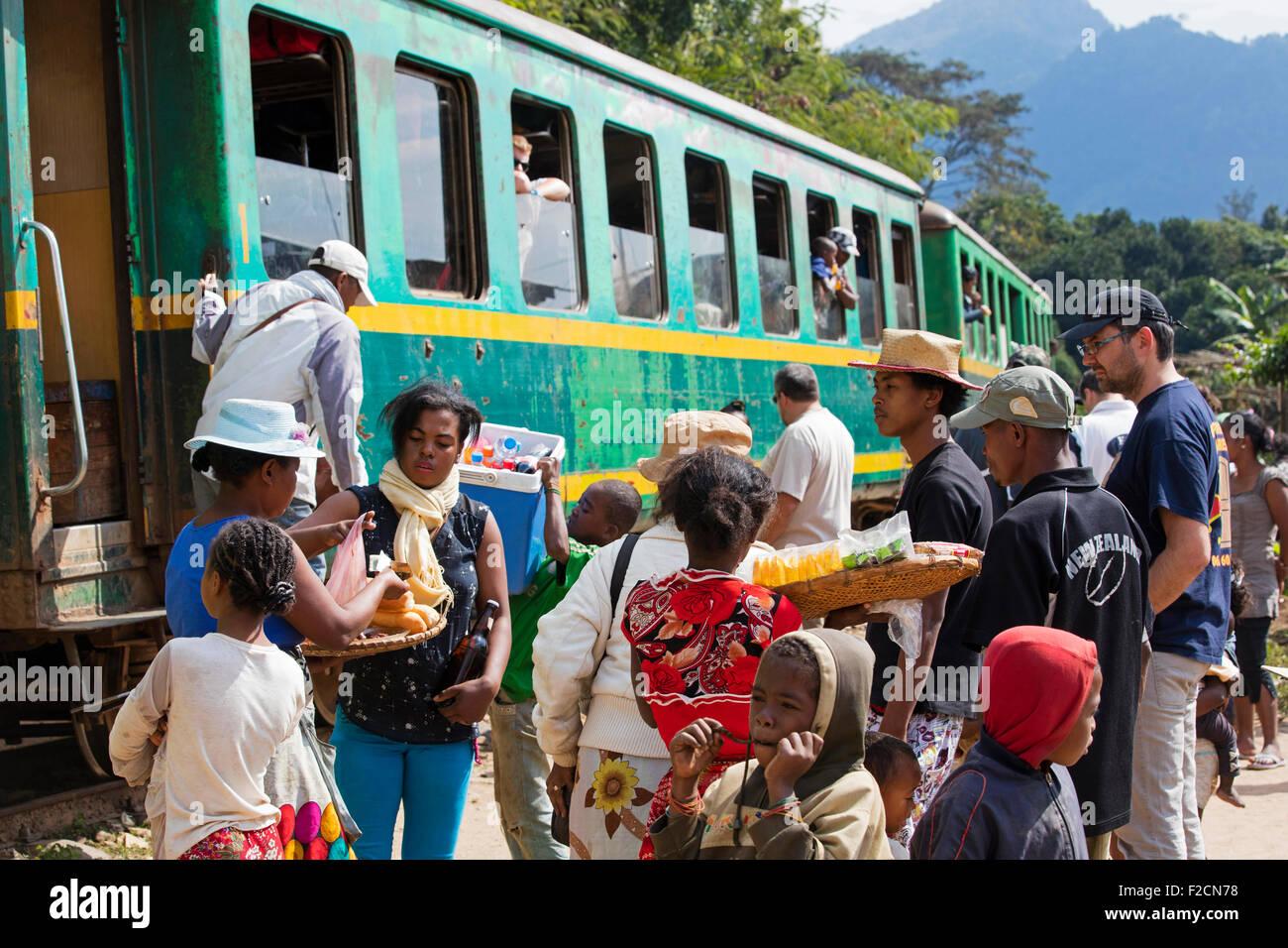 Vendors selling food on platform of railway station to passengers boarding train from Fianarantsoa to Manakara, - Stock Image