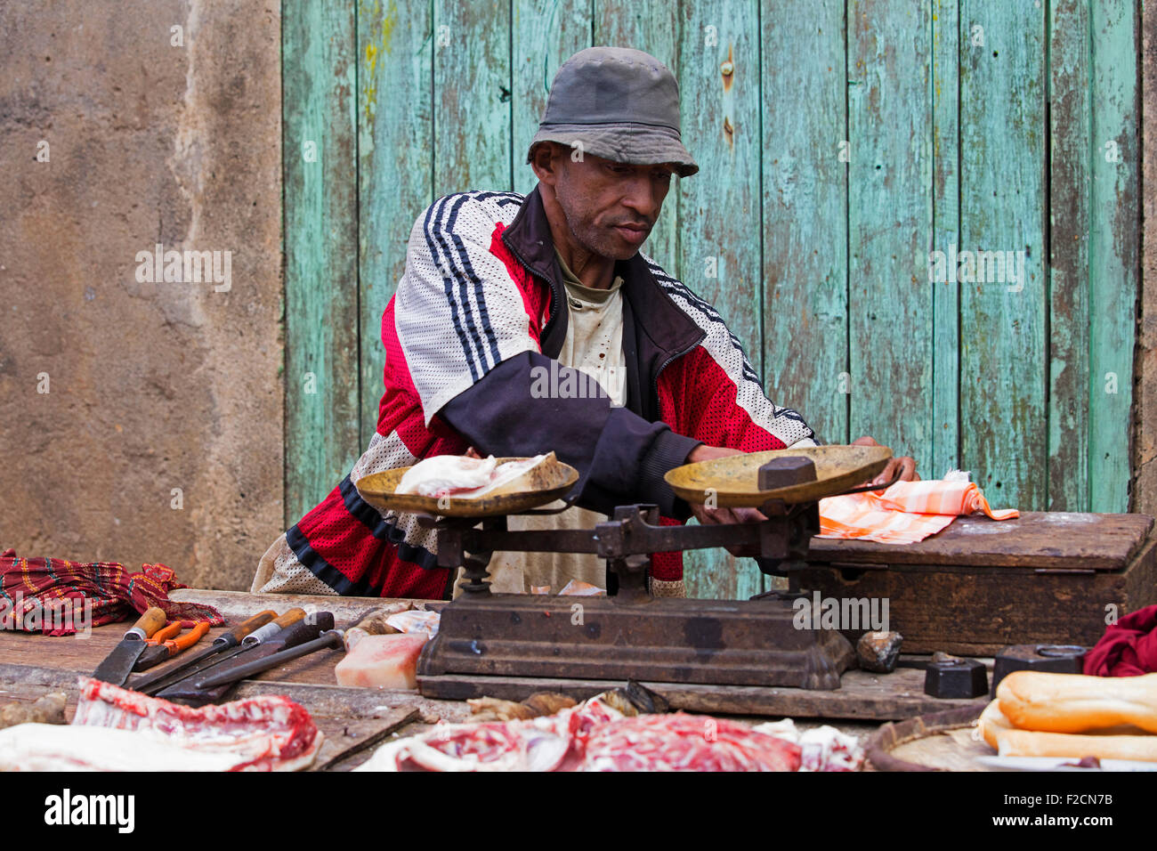 Malagasy butcher selling meat in open air butcher's shop, Madagascar, Southeast Africa - Stock Image