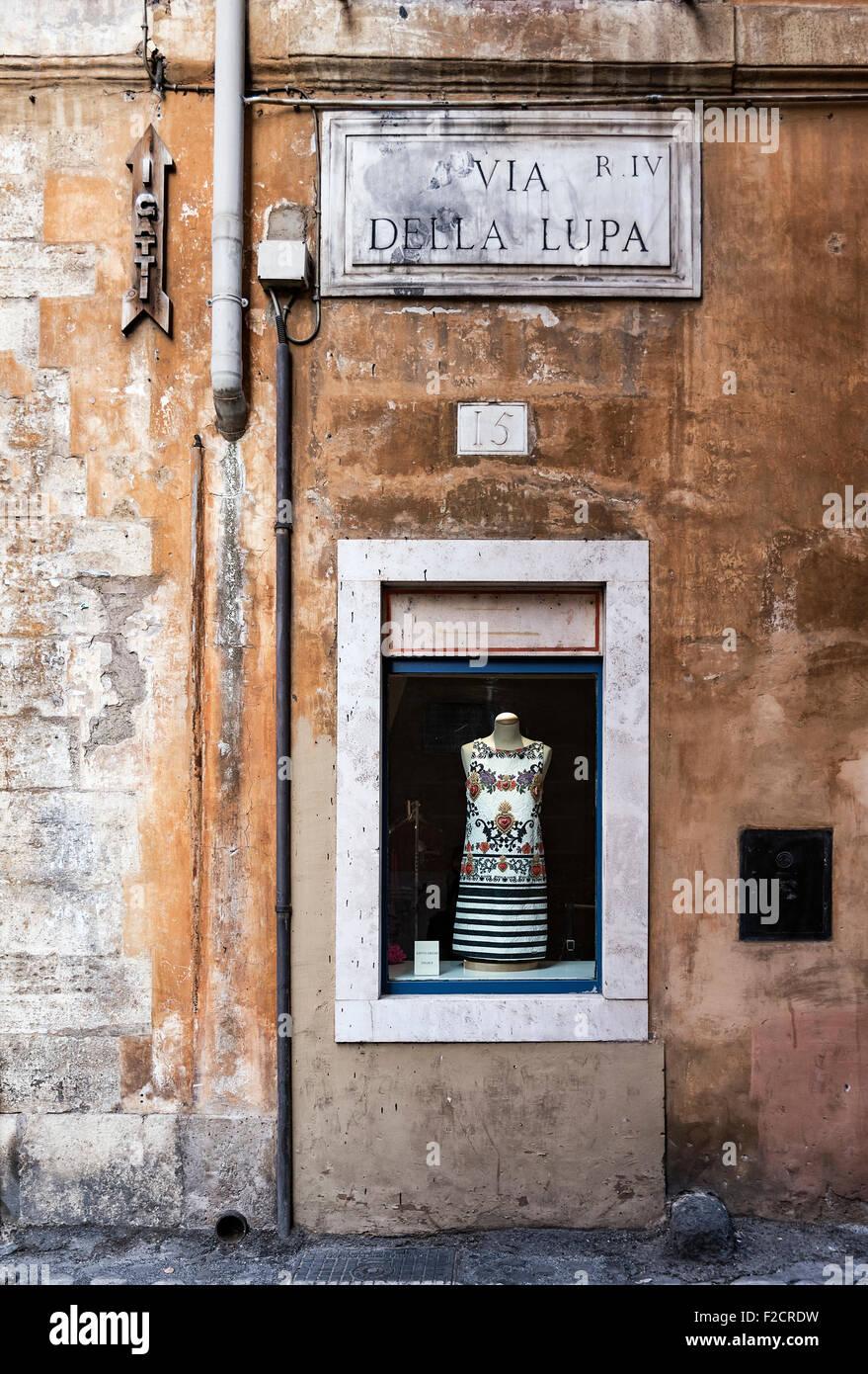 Dress shop window display on old street, Rome, Italy - Stock Image