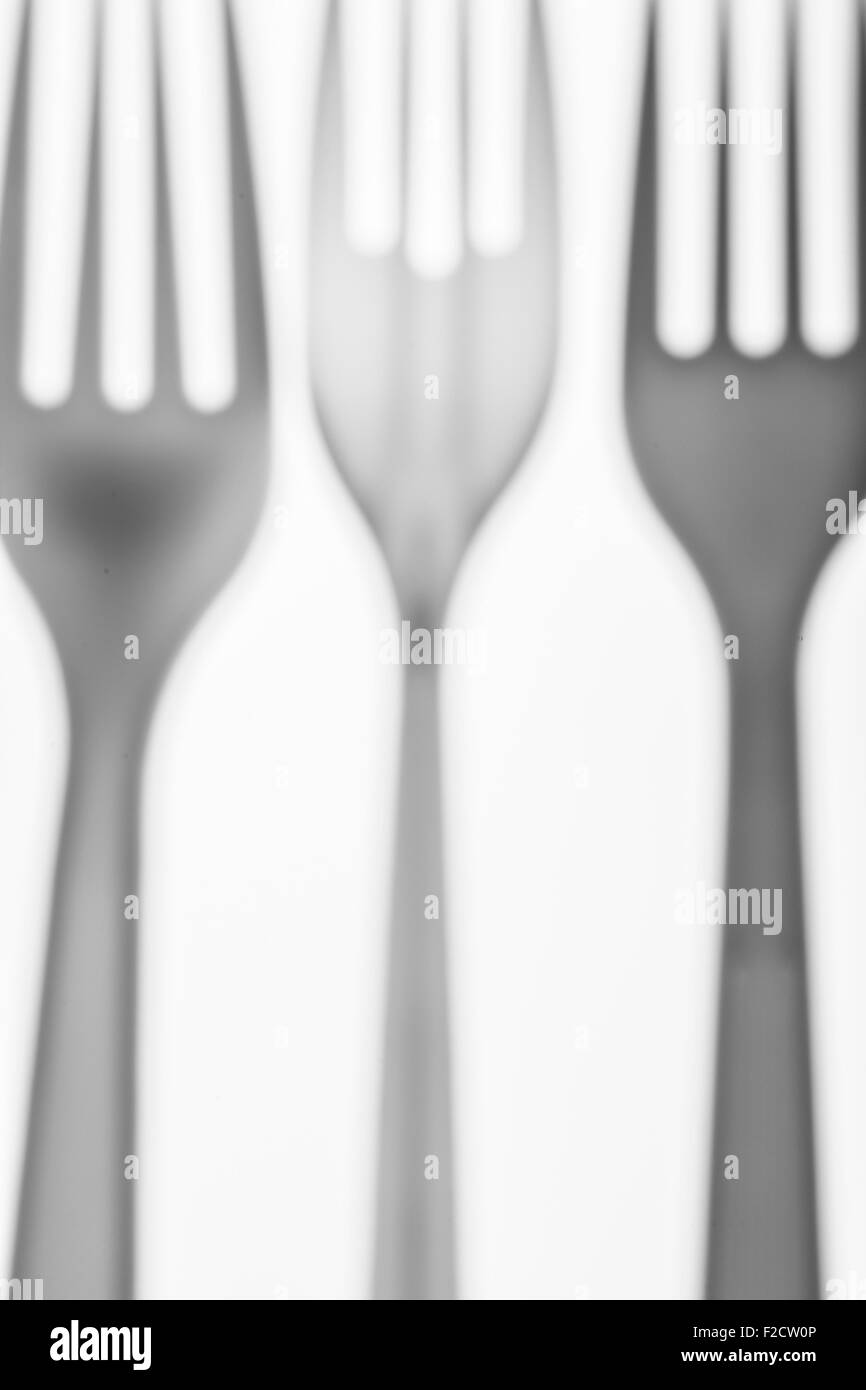 three out of focus, translucent, plastic forks, lined up - Stock Image