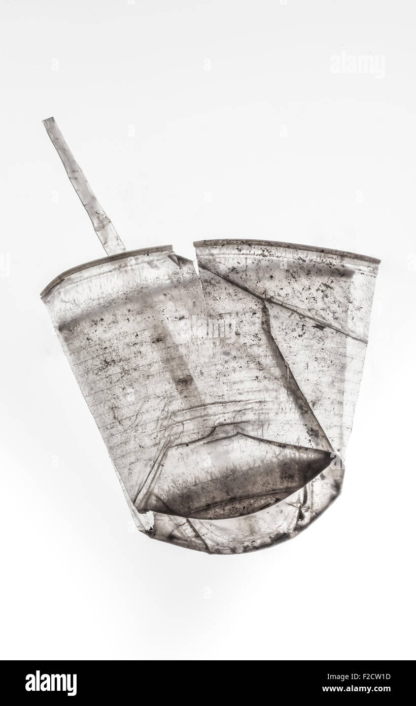 Dirty, plastic, flattened cup with straw on white background - Stock Image