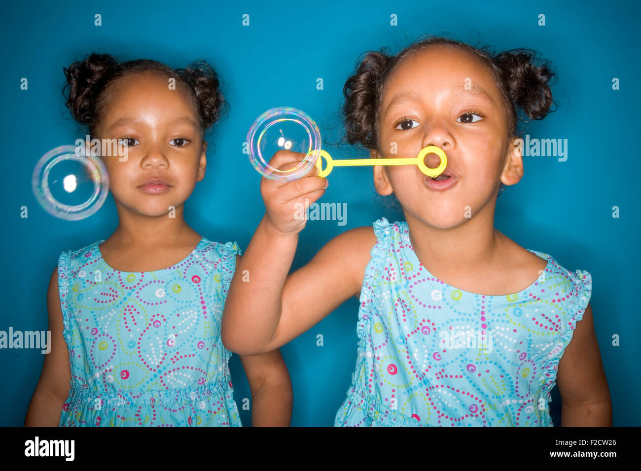 Identical twin black girls wearing matching clothes blow soap bubbles in studio setting stock image