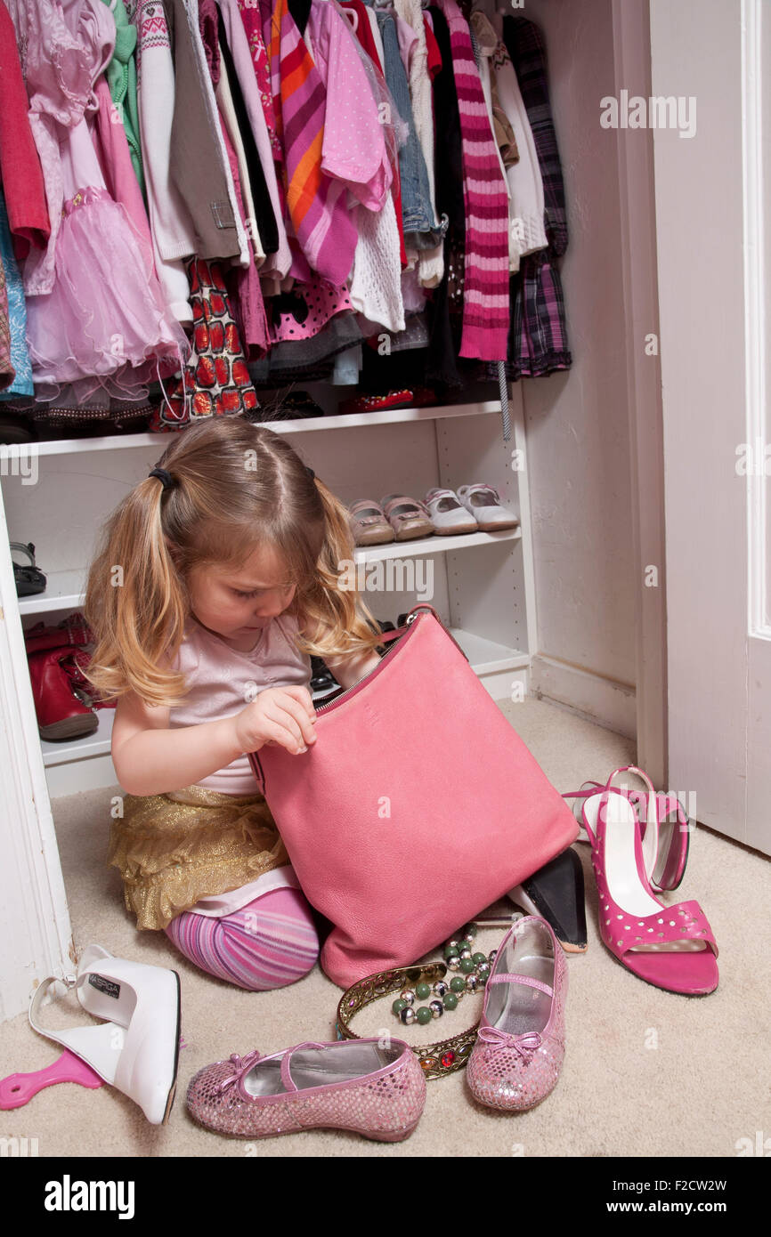 Young girl sitting in front of her closet looks in large pink purse with shoes surrounding her. - Stock Image
