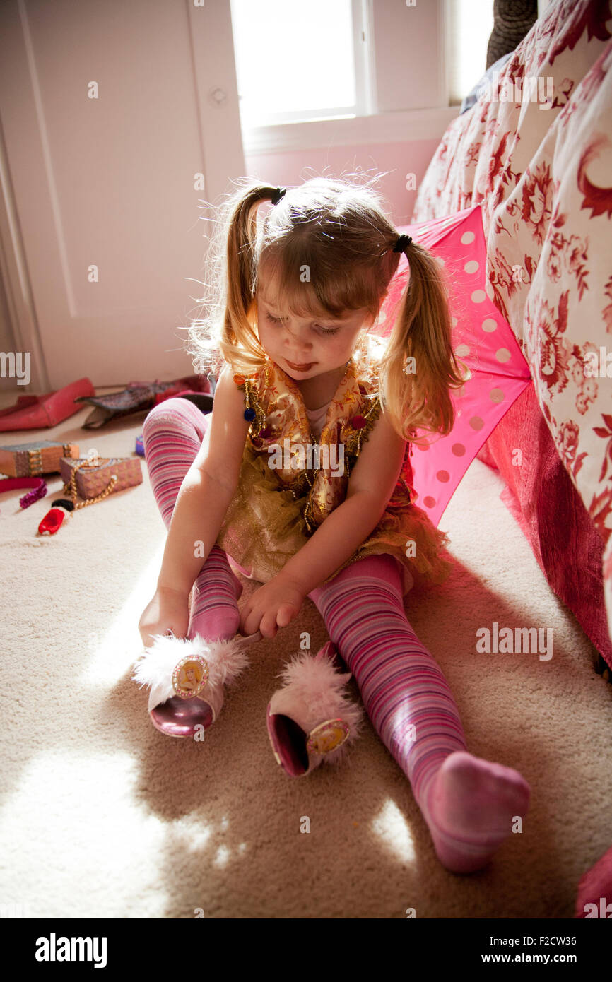 Young girl in pink plays sits on floor with bright light behind her, trying on shoe, playing dress-up in her bedroom - Stock Image