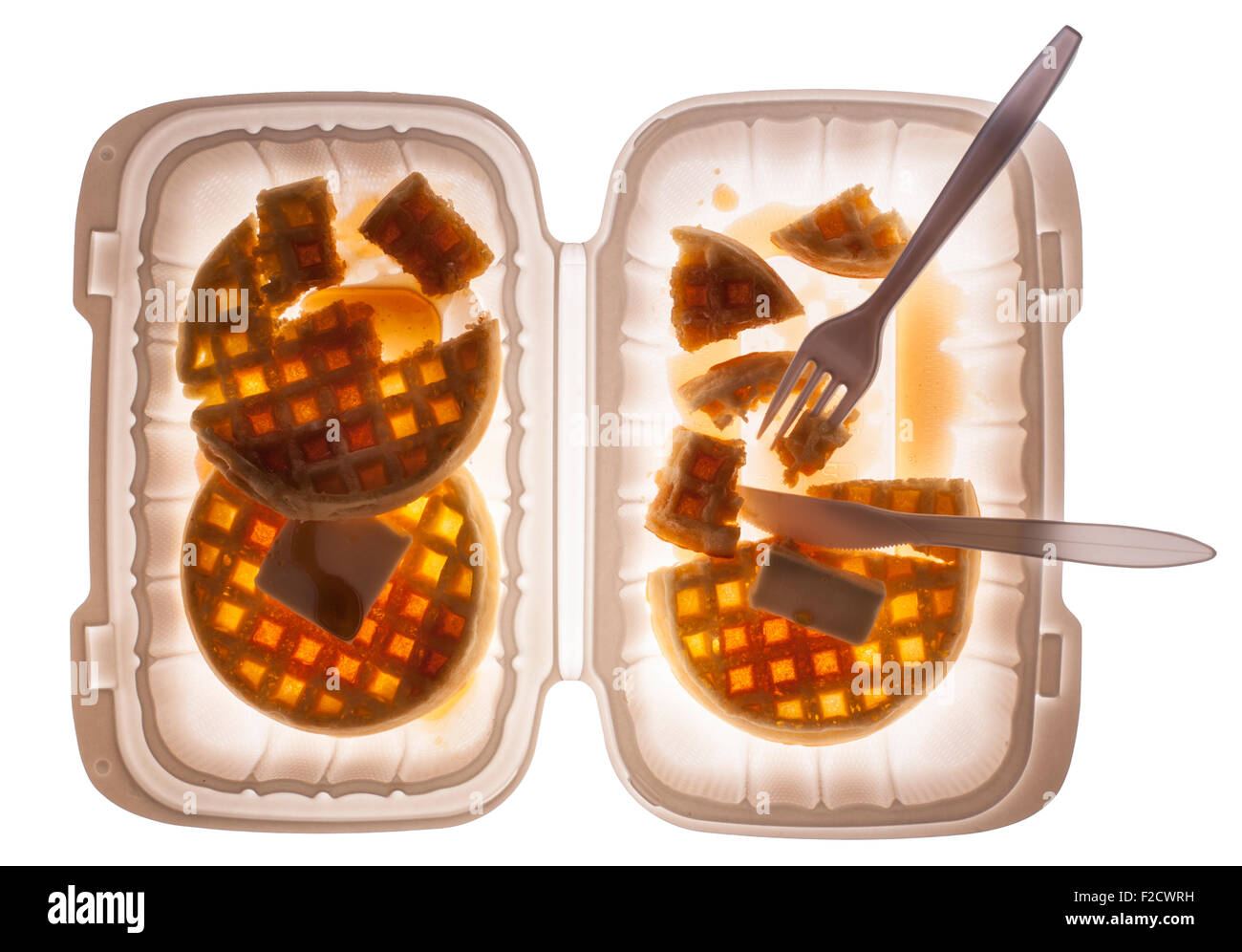 Looking straight down on waffles with butter and syrup in a plastic container with a fork and knife, half-eaten - Stock Image