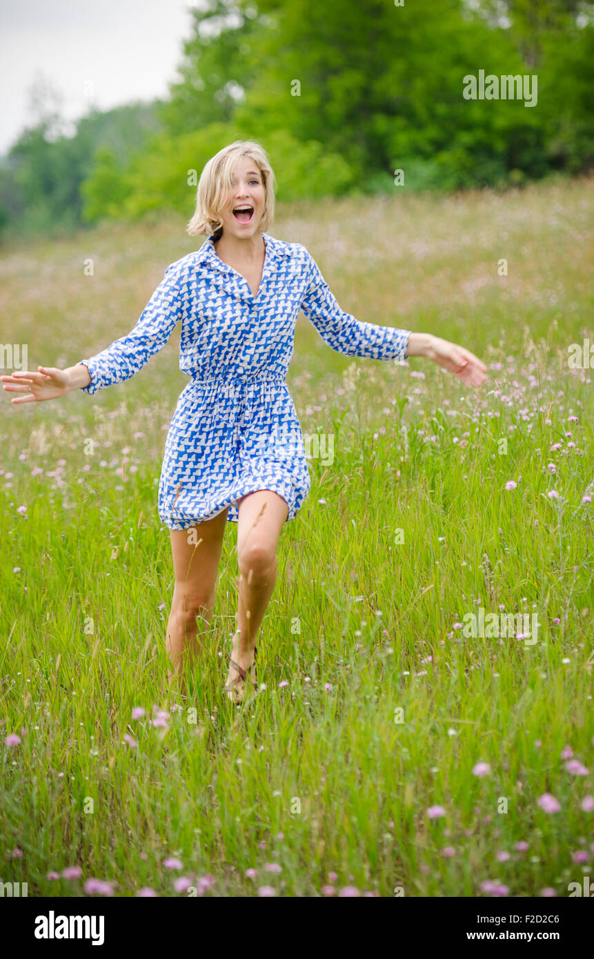 Girl with Blonde Hair Runs Through Field in Blue Dress while Laughing and Waving Her Arms - Stock Image