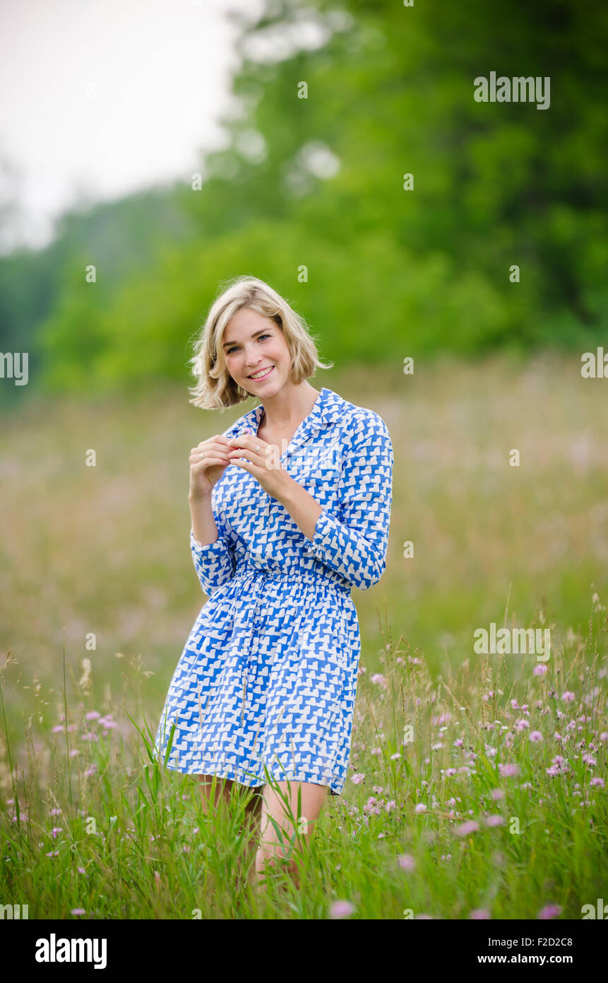 Beautiful Teenage Girl Stands in Field Wearing a Blue Dress with Green Trees in Background - Stock Image