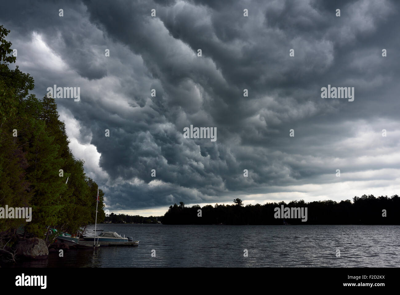 Early stages of dark clouds before a severe thunderstorm over Lake Cecebe in cottage country of Magnetawan Ontario - Stock Image