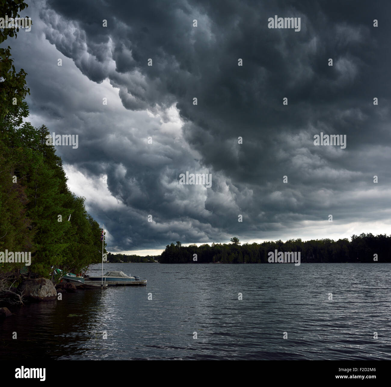 Swirling dark clouds before a thunderstorm over Lake Cecebe in cottage country of Magnetawan Ontario - Stock Image