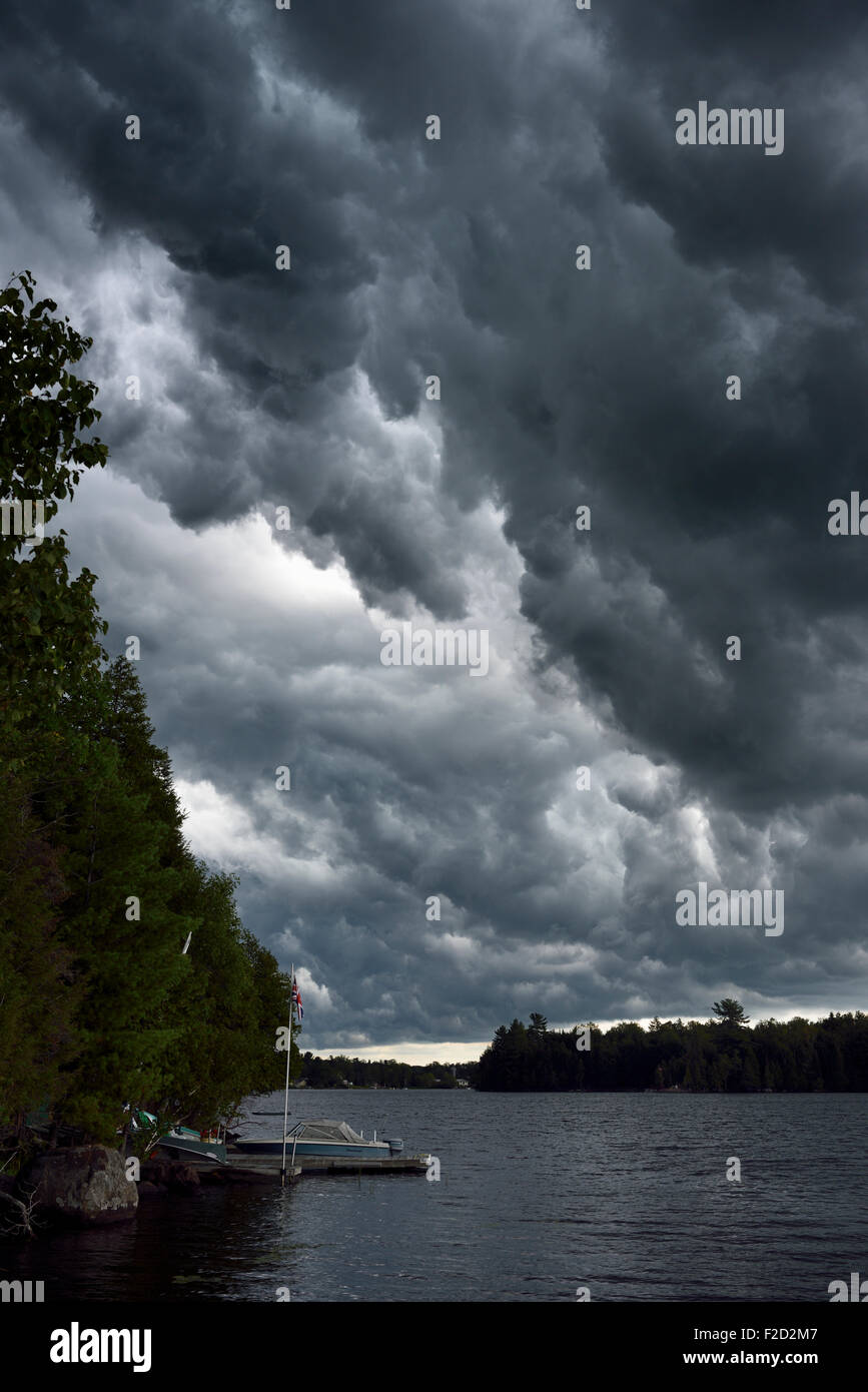 Dark clouds before a thunderstorm over Lake Cecebe in cottage country of Magnetawan Ontario - Stock Image