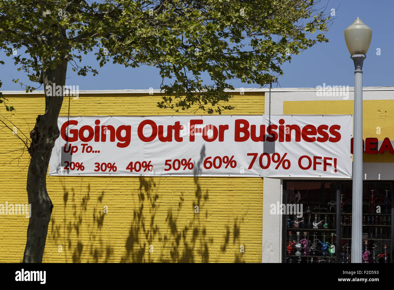 Going out for business sign on the side of a yellow painted store wall - Stock Image