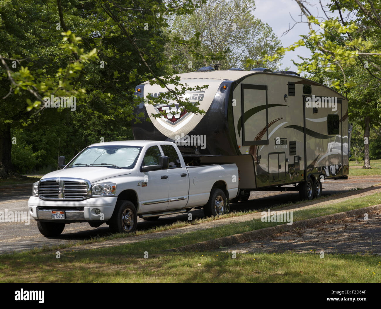 2008 Dodge Ram 3500 long bed pickup with a Winnebago 33ck fifth wheel trailer hitched up parked in a leafy rest - Stock Image