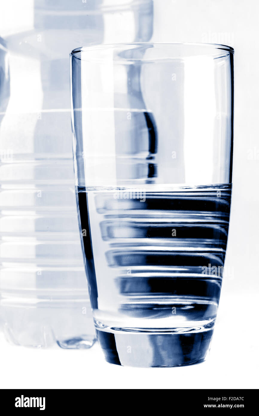 Glass of water in front of water bottle isolated on white - Stock Image