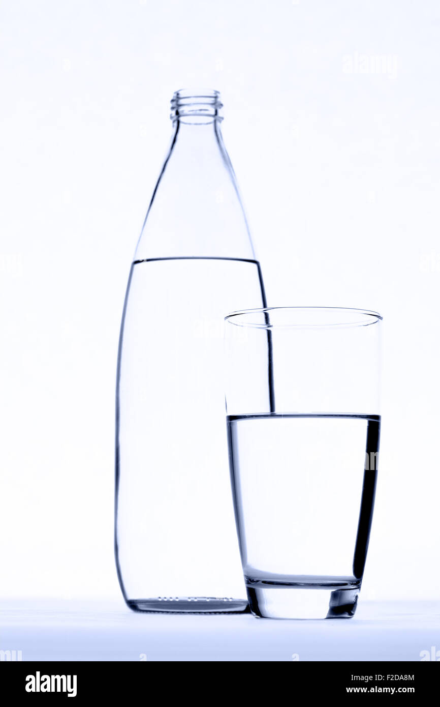 Glass of water in front of water bottle isolated on white. - Stock Image