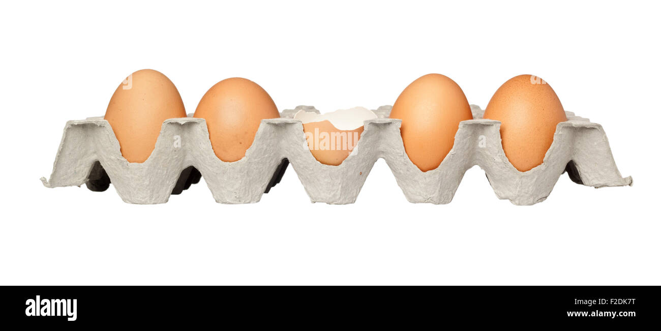 One cracked egg in a tray of eggs isolated on white background - Stock Image