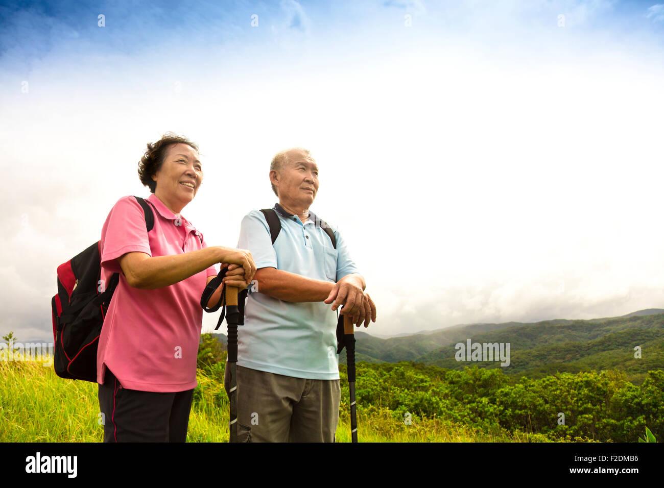 happy senior couple hiking on the mountain - Stock Image