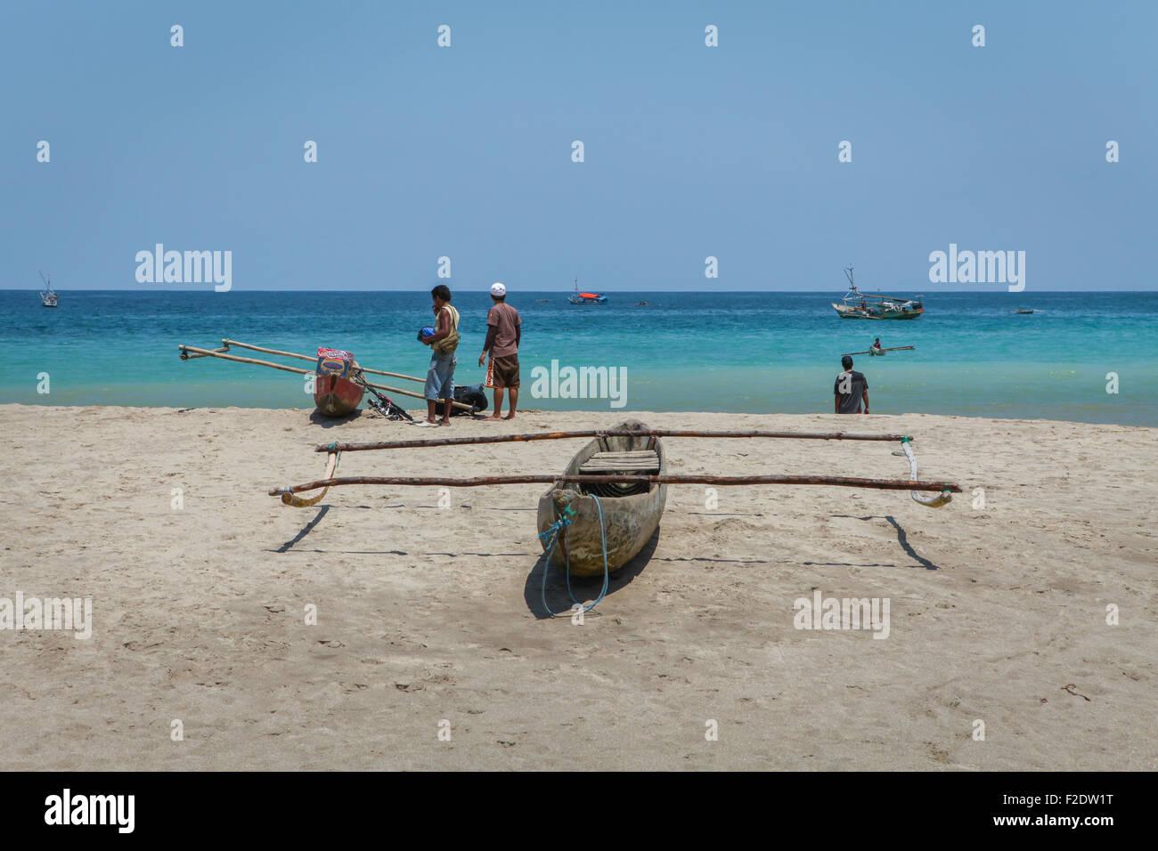 Men And Wooden Canoe At Tropical Beach Of Sumba Island Facing Indian Ocean