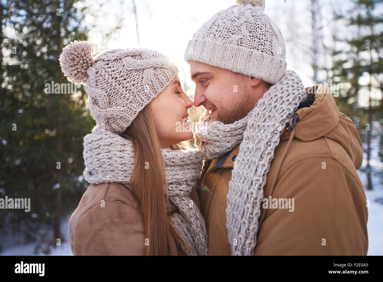 Happy young man and woman in winterwear flirting outside - Stock Image