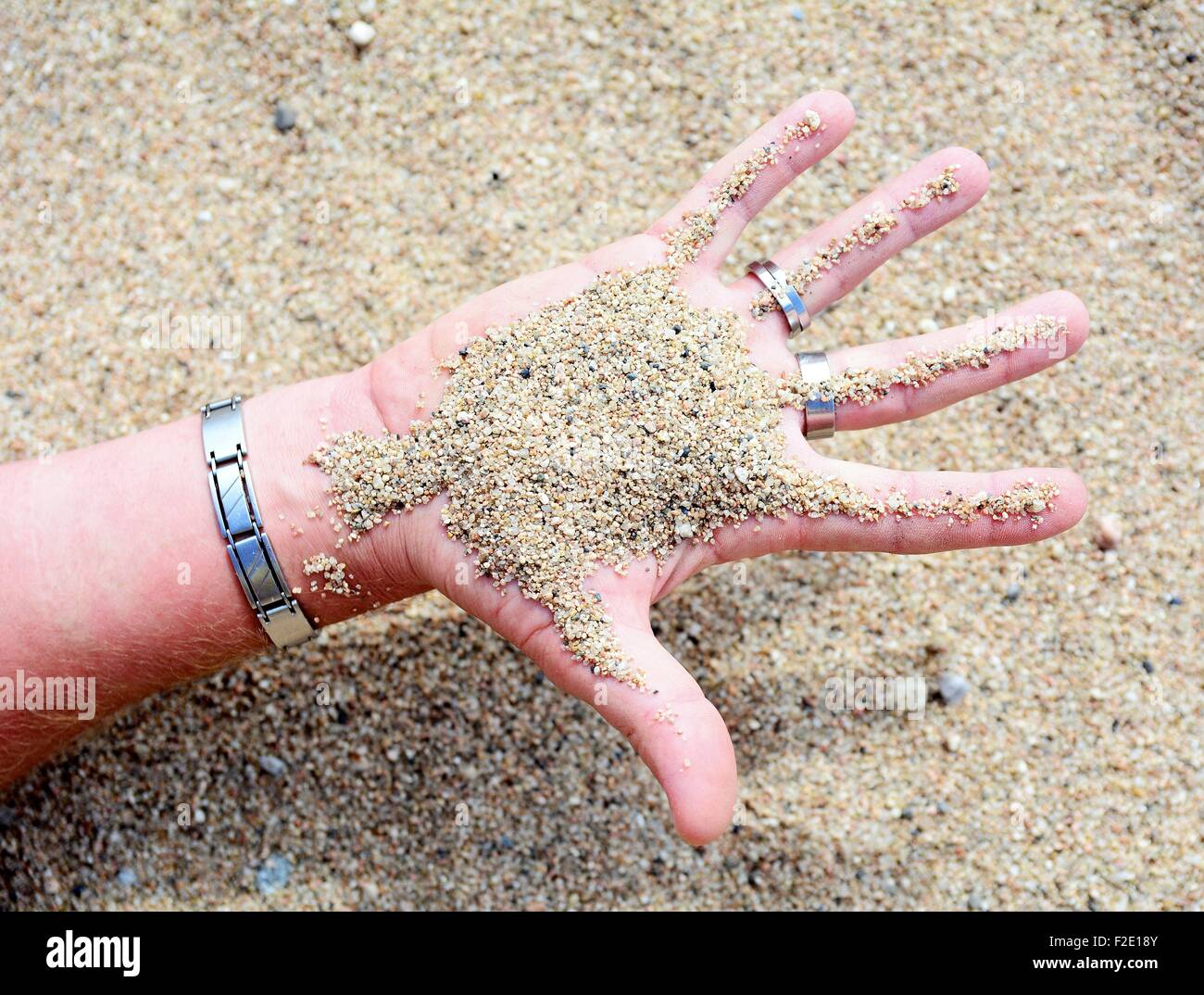 Conceptual shot of the sand in the palm of men's hand. - Stock Image