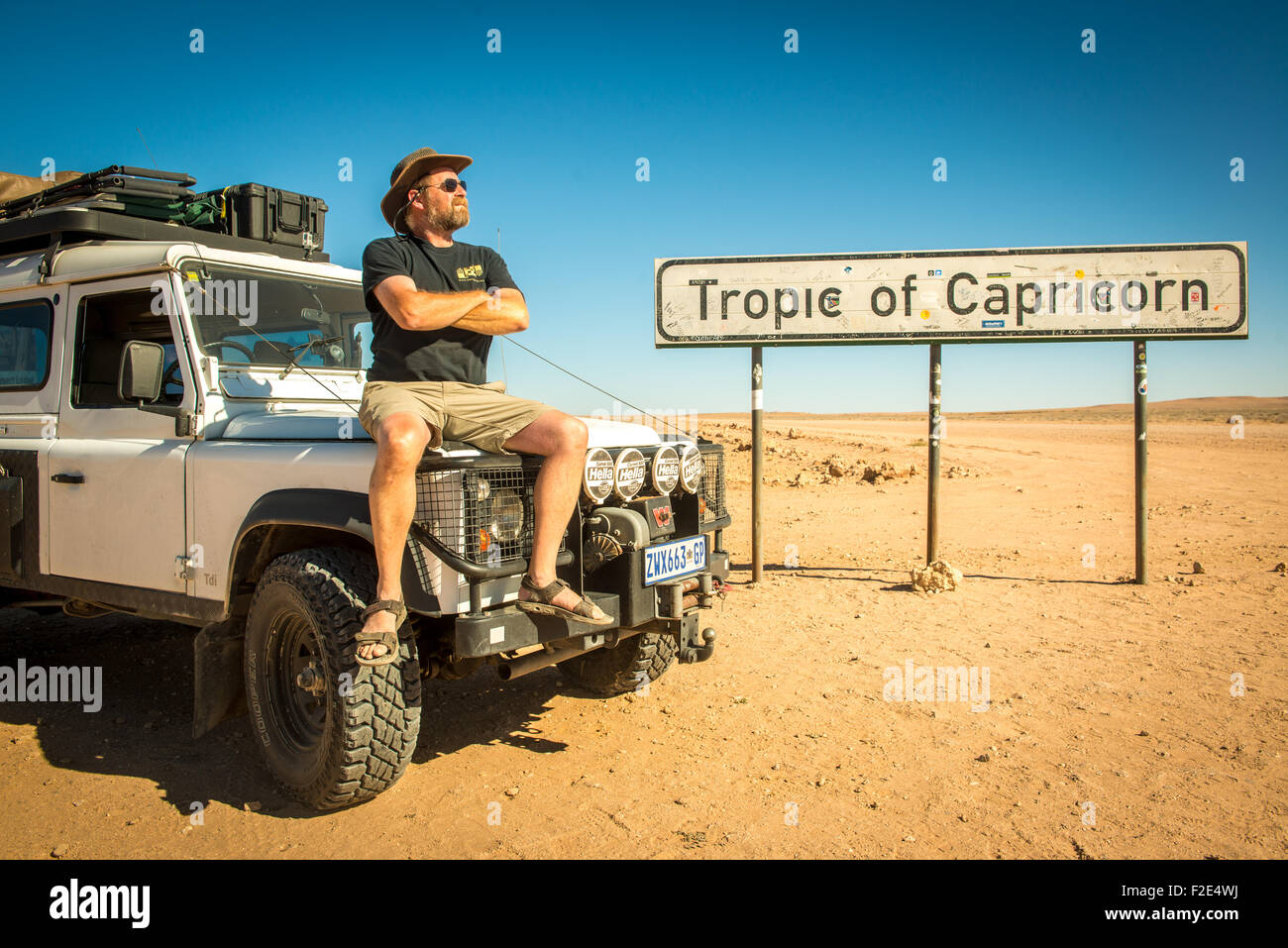 Man sitting on his Land Rover Defender 110 parked in the desert next